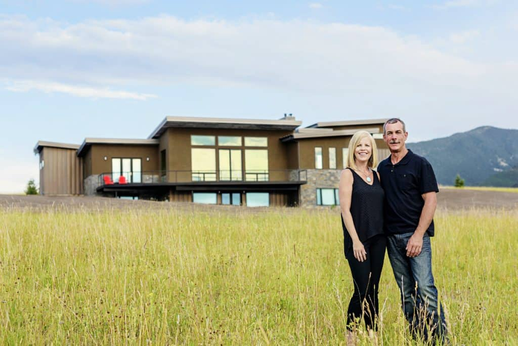 Photo of Tom, CEO of Schafer Construction, & his wife, Joan Schafer standing in a field before a custom modern home.